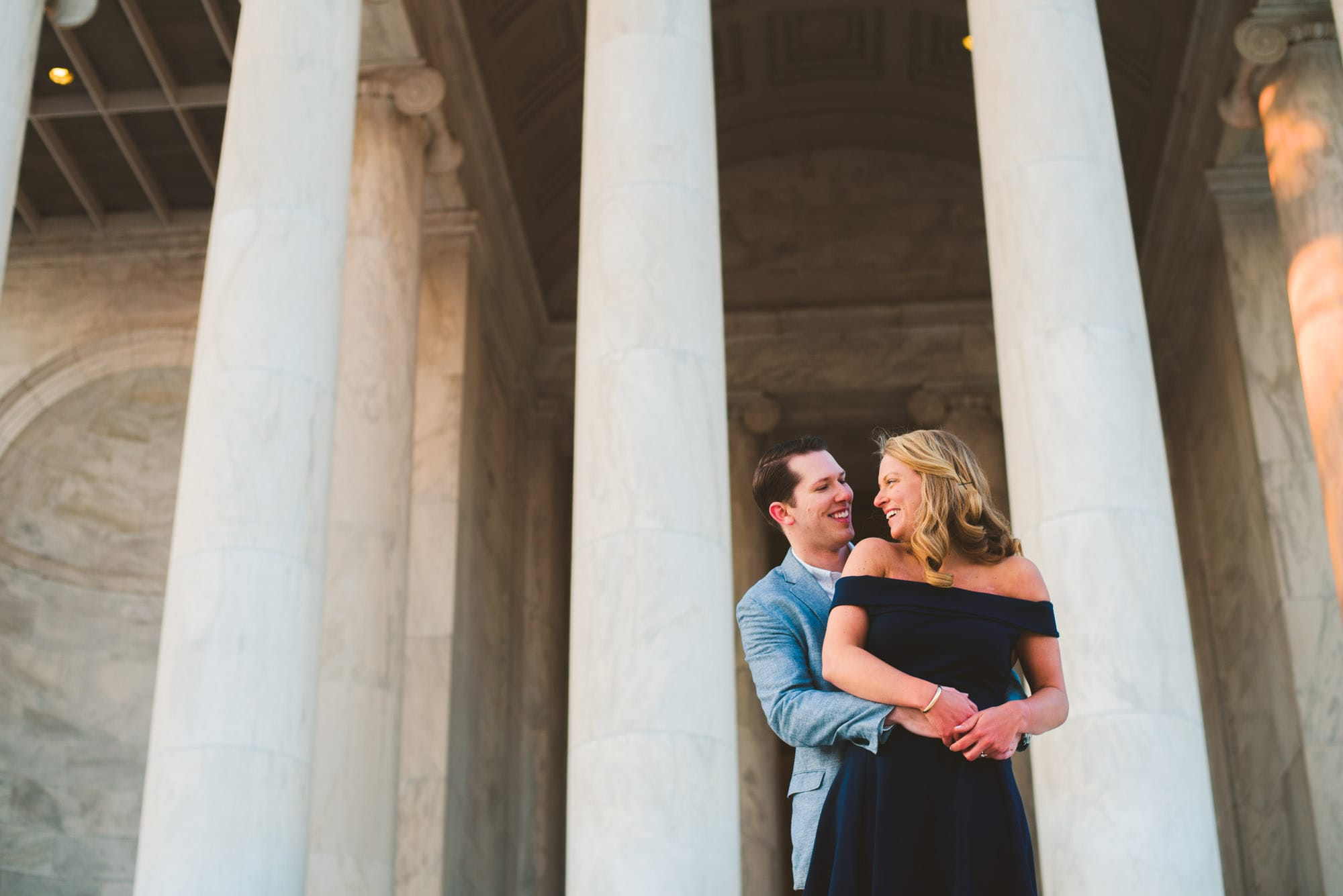 couple laughing in front of the Jefferson memorial during their engagement session in washington DC.