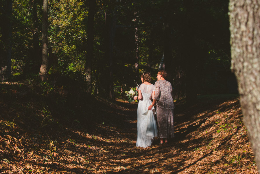 Mom and a bride walk the tree lined lane up to the ceremony site at Yesterday Spaces