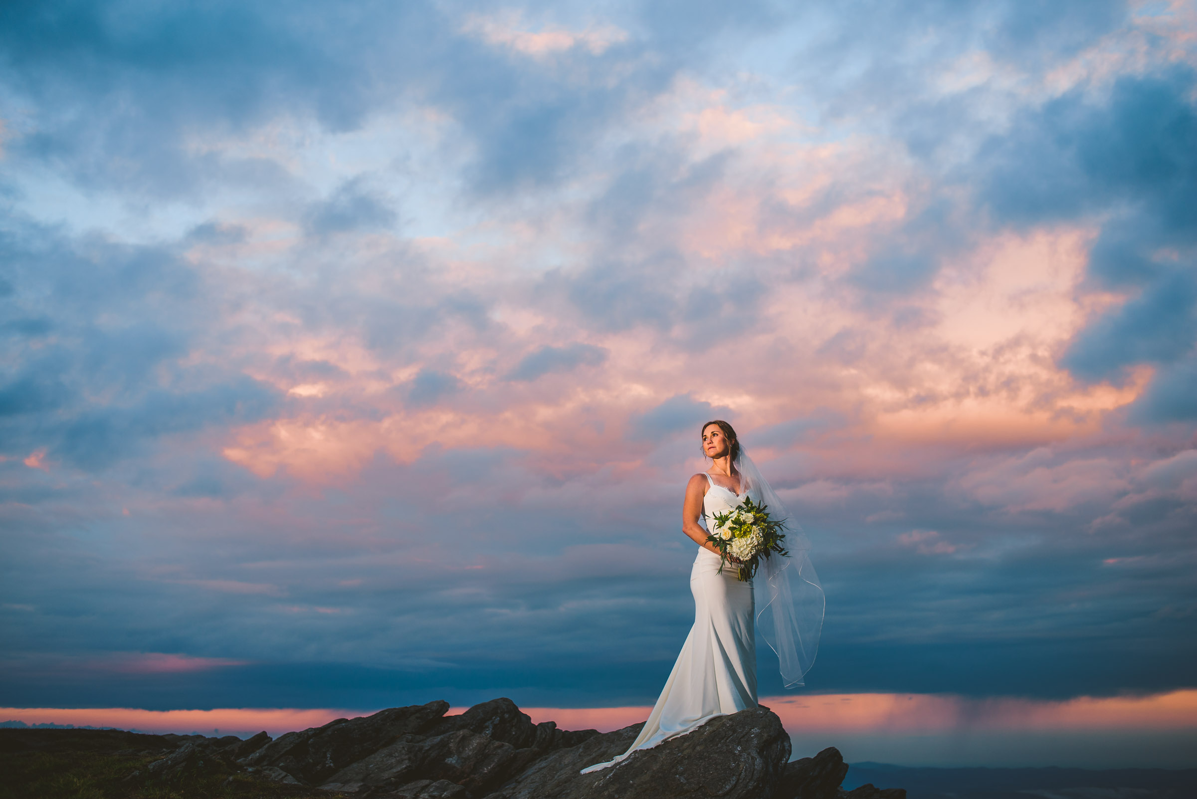 Gorgeous bride on a mountaintop with a sunset behind her