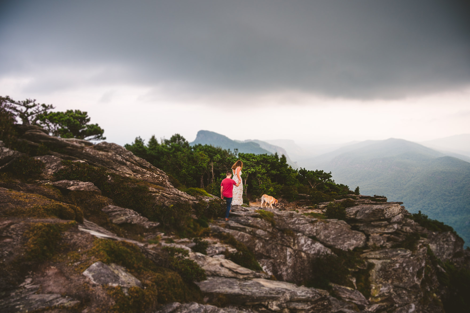 Couple hikes the side of Hawksbill Mountain during their Linville Gorge Engagement Session