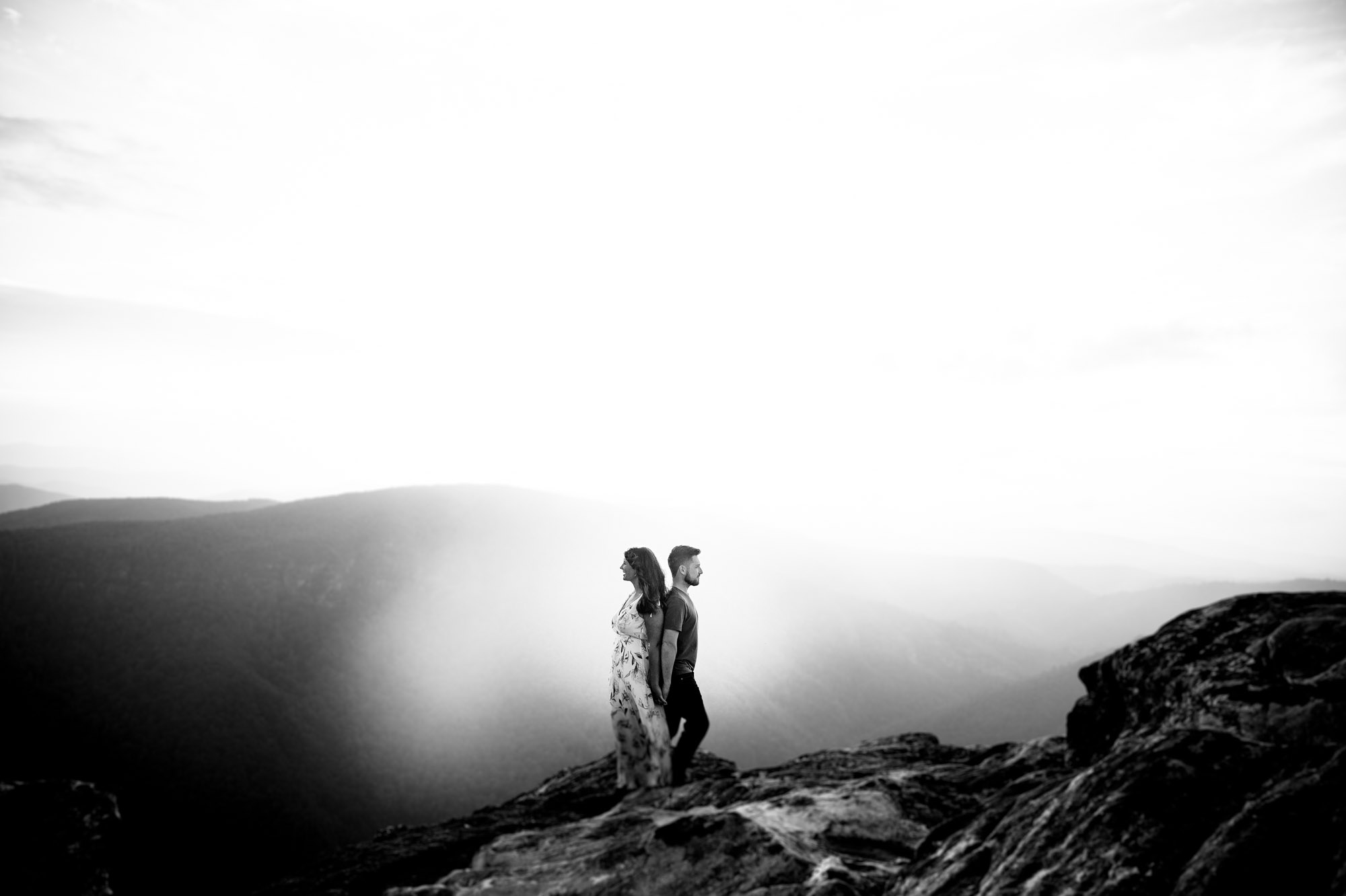 Couple stands back to back during their mountain engagement session