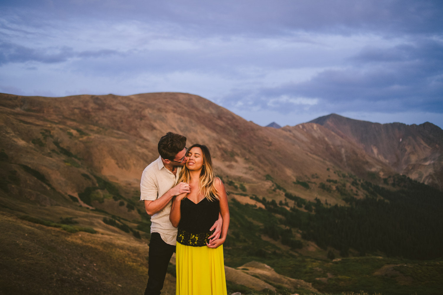 Loveland Pass elopement photo of couple at sunset with Colorado mountain peaks behind