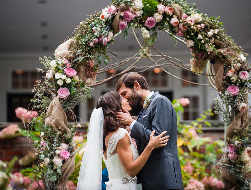 Bride and groom kiss during their wedding ceremony in front of a flower alter